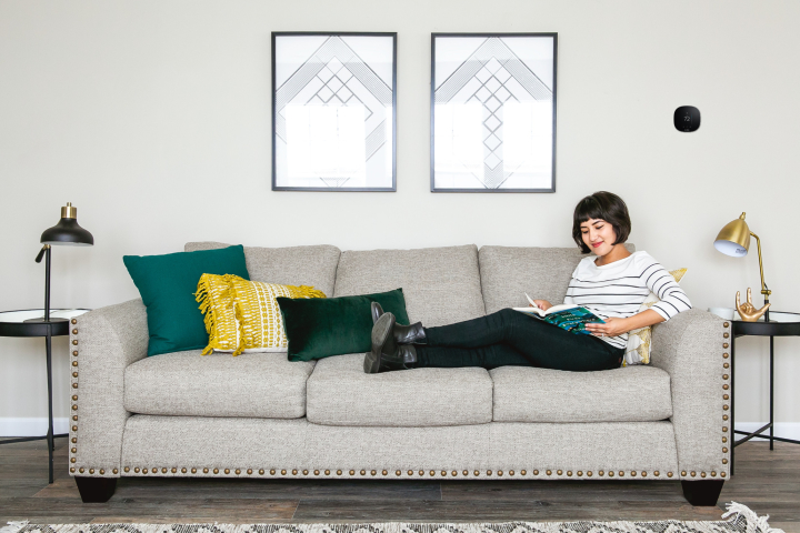 Woman sitting on a couch in a manufactured home living room with an ecobee thermostat on the wall.