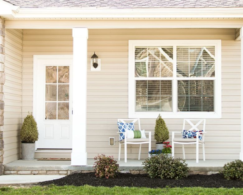 Manufactured home porch with white columns.