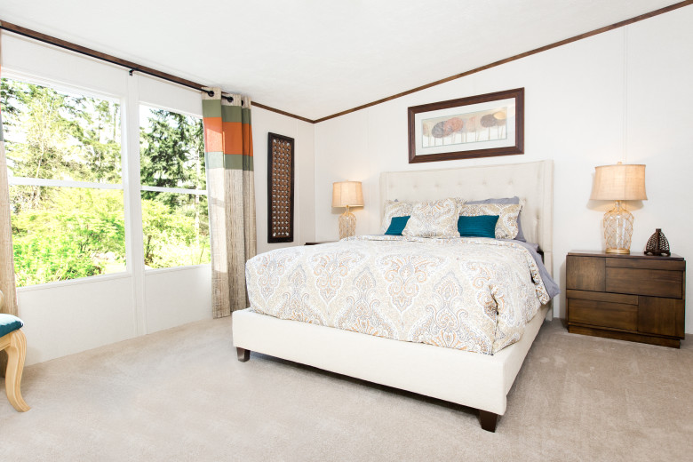 Manufactured home bedroom with large white bed in the middle of the room and window feature.