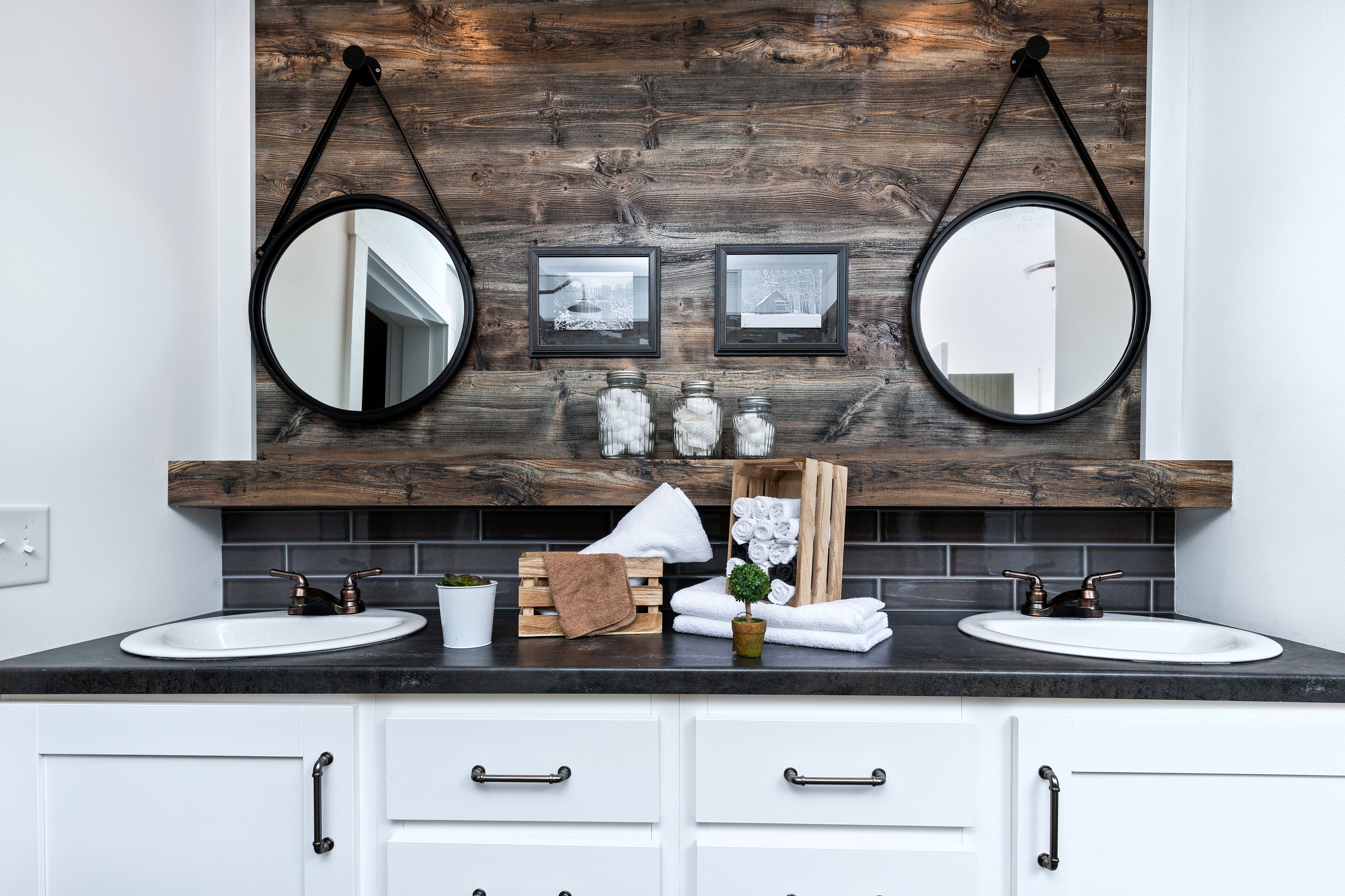 Mobile home primary bathroom with a large wooden accent wall behind double sinks.