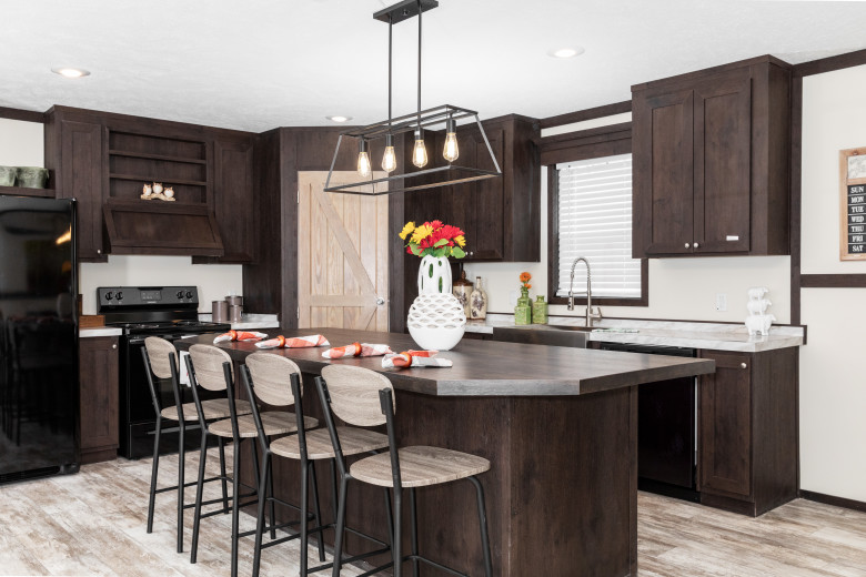 Manufactured home kitchen with dark wooden cabinets and a large breakfast bar.