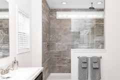 Gray tile in the shower of a white manufactured home master bathroom.