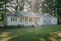 The Laney manufactured home model with white and gray siding, a large front porch, lawn and trees behind it.
