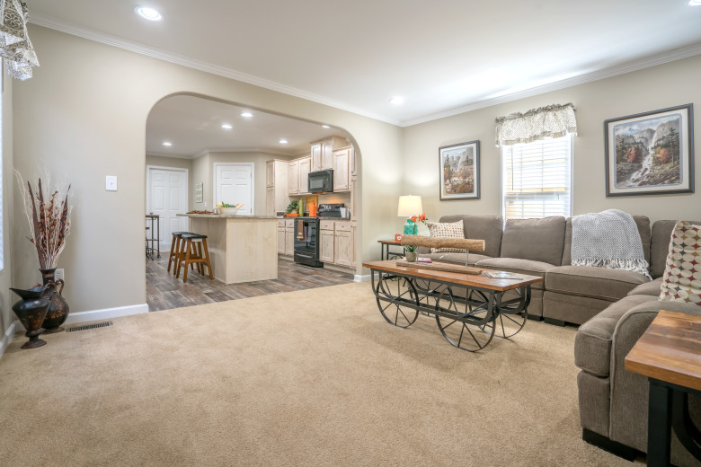 Manufactured home living room with carpet and a large entryway into the kitchen.