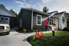 Women and daughter outside of their dark gray CrossMod™ home with a detached garage.