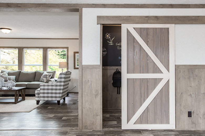 White and light brown sliding barn door, half open, showing a closet behind it, in a white wall with light brown wainscoting and a living room to the left.