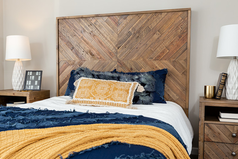 Bedroom with reclaimed wood headboard and yellow, navy and white bedding, with 2 matching wood bedside tables with white lamps and books.