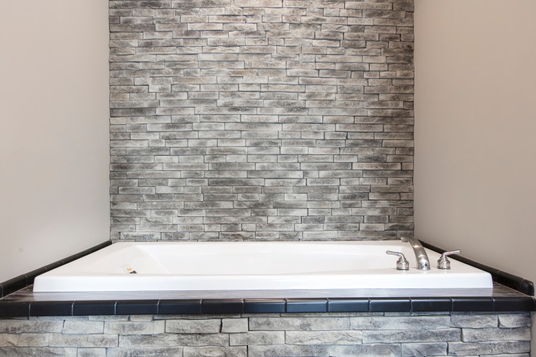 A large bathtub in a manufactured home surrounded by stone on all sides and stone accent wall behind it.