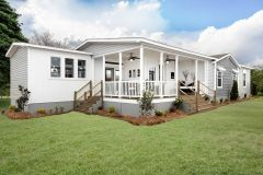 An exterior shot of a manufactured home featuring a large covered porch and two sets of stairs.