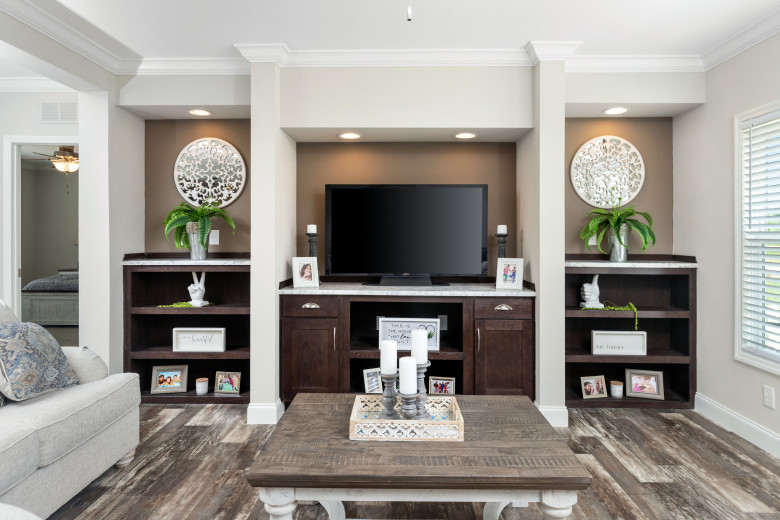 A built-in entertainment center with dark stained wood, cabinets and shelving.