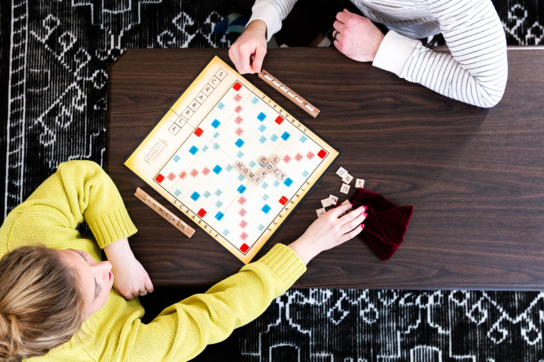 A young couple plays a word based board game on a wooden coffee table.