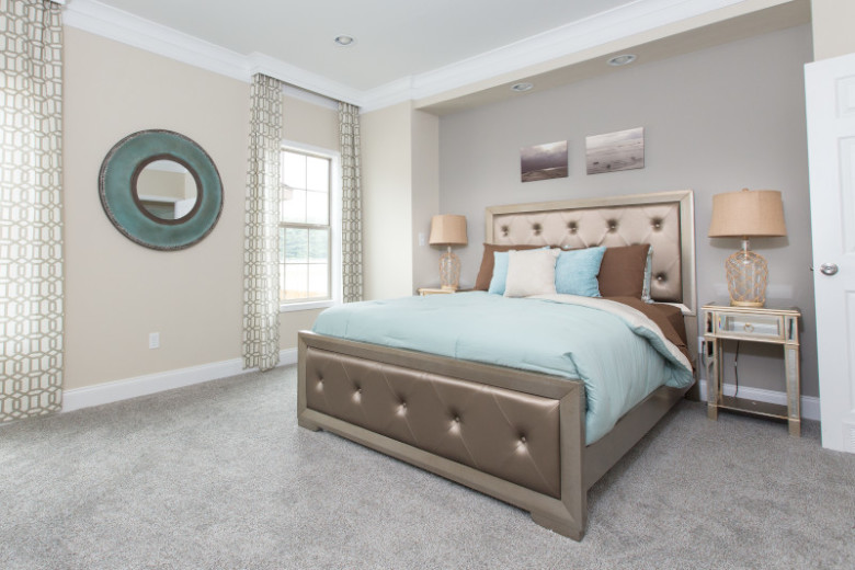 Blue and gray bedroom in a manufactured home featuring recessed lighting and gold bed and nightstands.