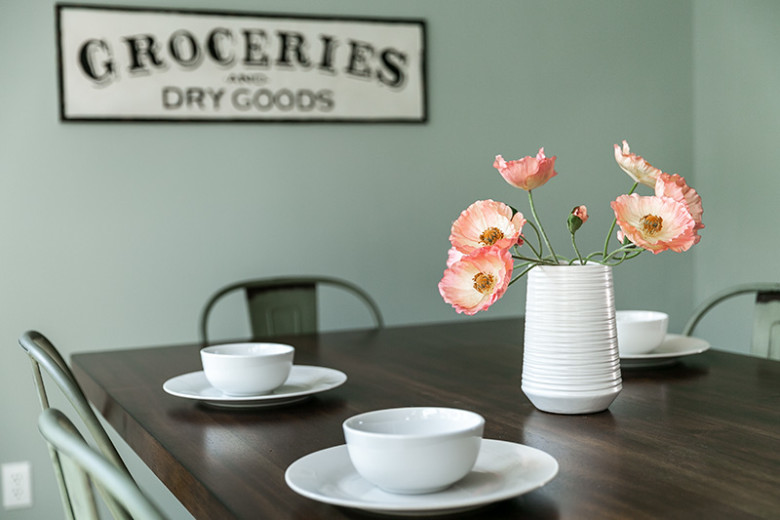 "Dark wood table and green metal chairs with 3 white plates and bowls and a white vase with pink flowers, with green walls behind it and a sign that reads ""Groceries and Dry Goods."""
