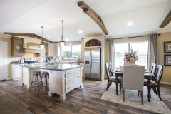 The Bordeaux kitchen is French country style and features a vaulted ceiling, frosted pendant lights and a kitchen island in a cream color.