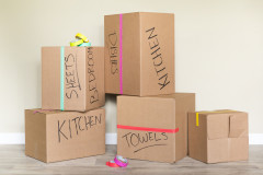 Labeled moving boxes sitting in a room of a manufactured home