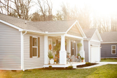 Exterior of a Manufactured home with a front porch and lawn.