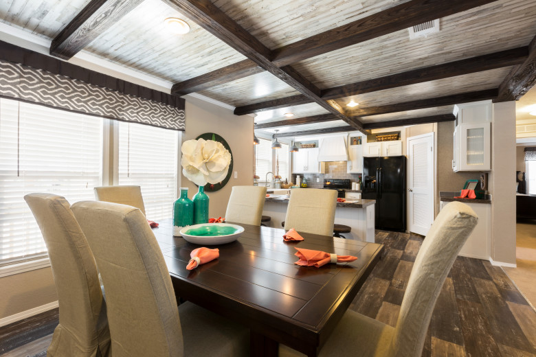 Dining room of the Drake model with dark wood floors and wooden ceiling beams.