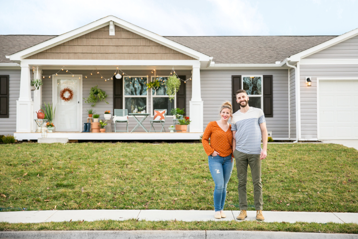 Couple outside a Clayton Built® home with green grass.