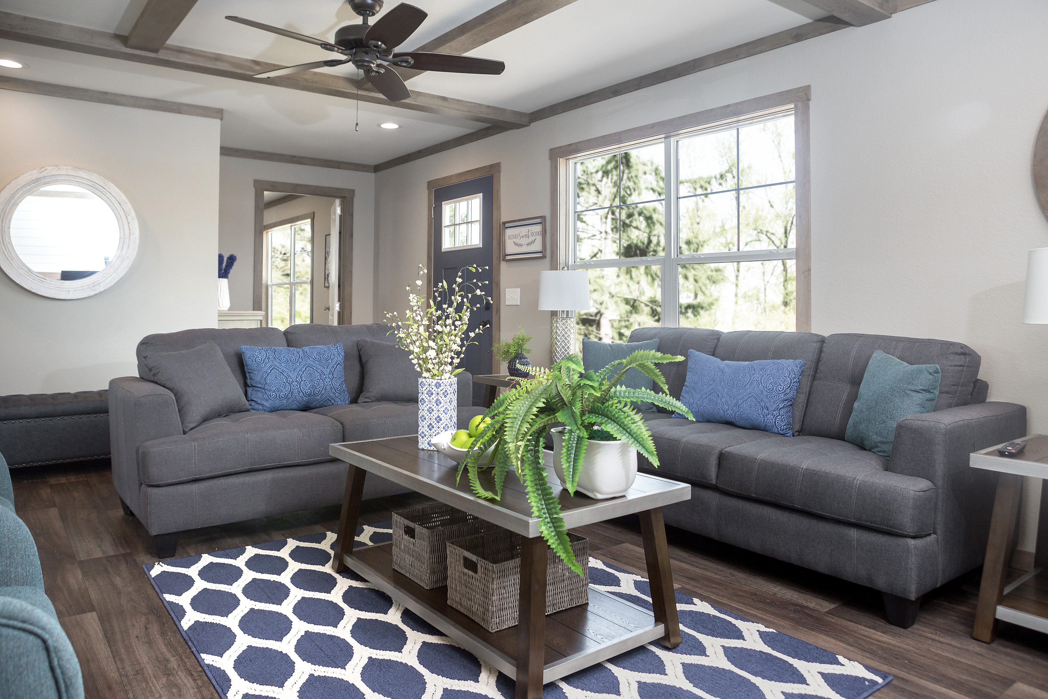 Manufactured home living room with grey couches, coffered ceilings and a round hanging mirror.