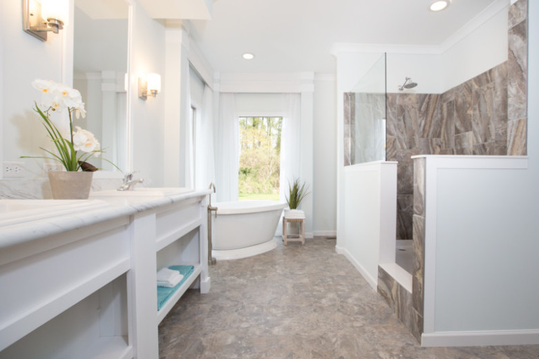 Primary bathroom with tiled walk-in shower and white soaker tub and dual vanity.