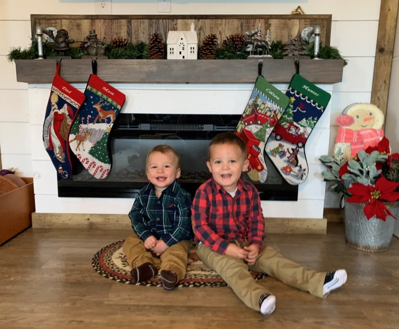 Two young boys in plaid shirts sitting on the floor in front of a fireplace.