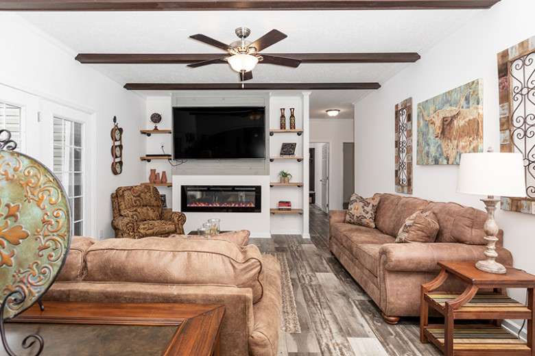 Den featuring accent wall with built-in shelves, TV and fireplace, as well as beams, ceiling fan, two couches and country decor.