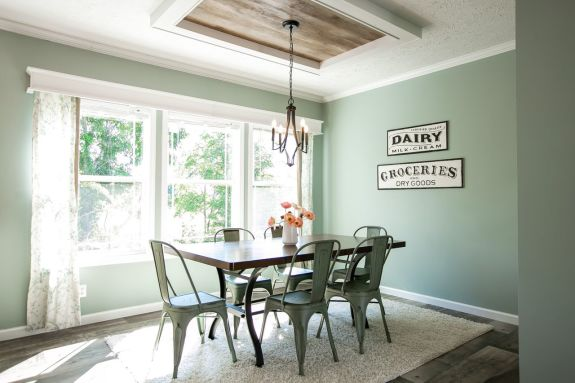 The pastel green wall paint in the Country Aire dining room makes this home feel modern while staying true to it's down home roots with farmhouse shiplap ceiling accents and more!