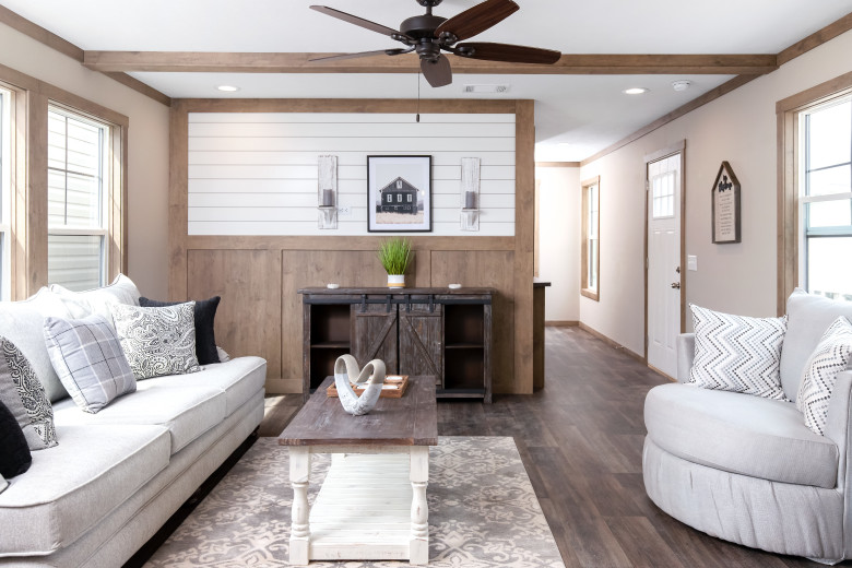 Manufactured home living room with a built-in shiplap accent wall and wooden ceiling beams.