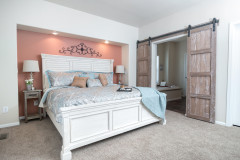 Bedroom of the Anniversary 3.0 model with white furniture and sliding barn doors.