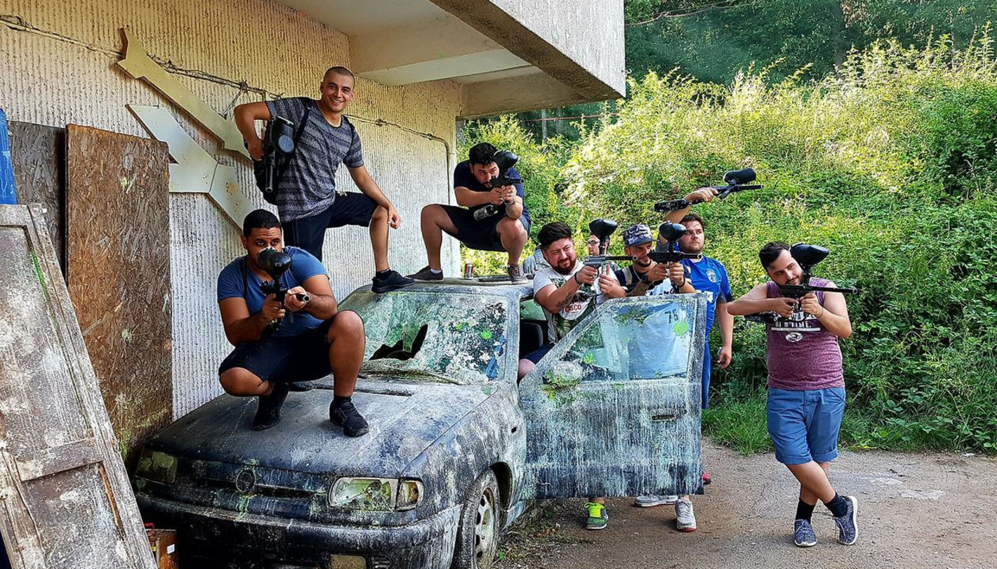 Swiss group standing on car for paintball