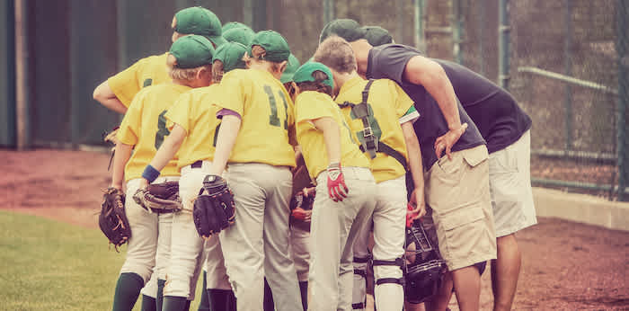 a youth baseball team and coaches huddling before a game