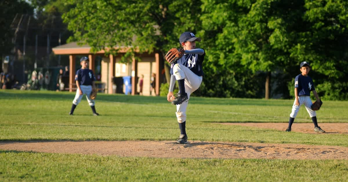 a youth baseball pitcher in a wind up about to strike out a batter