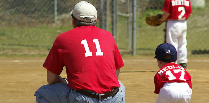 a youth sports coach with a baseball player