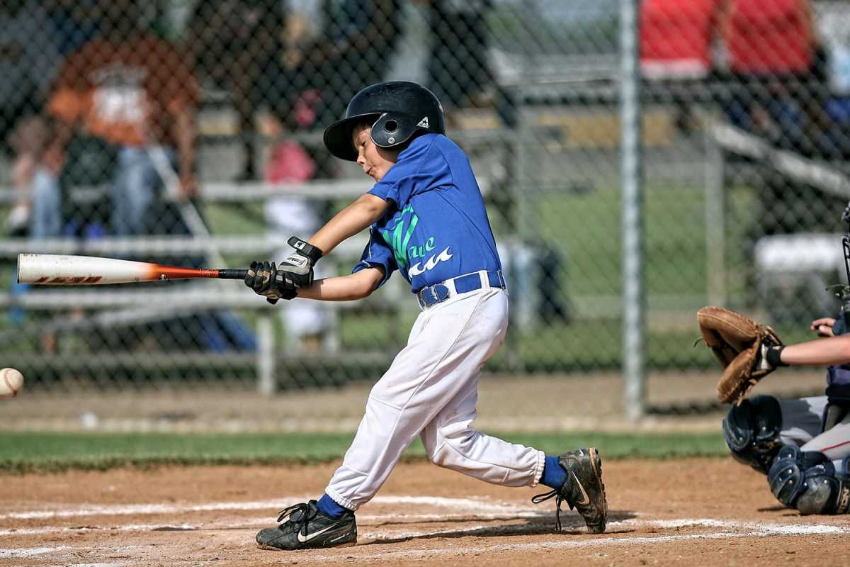 a youth baseball player getting a hit during a game