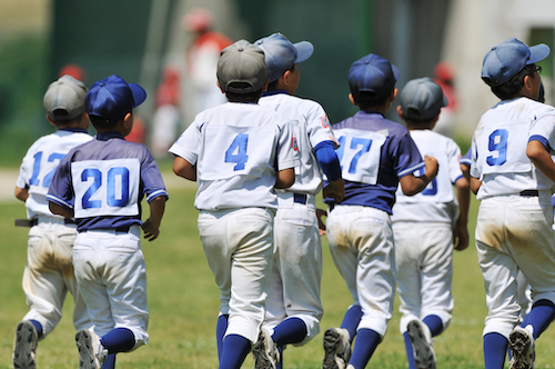 youth baseball players running onto a field