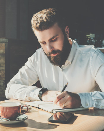 A bearded male writer taking notes for his novel.