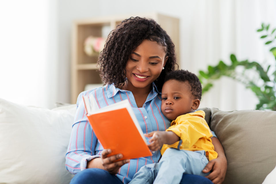 Mother reading to boy on couch