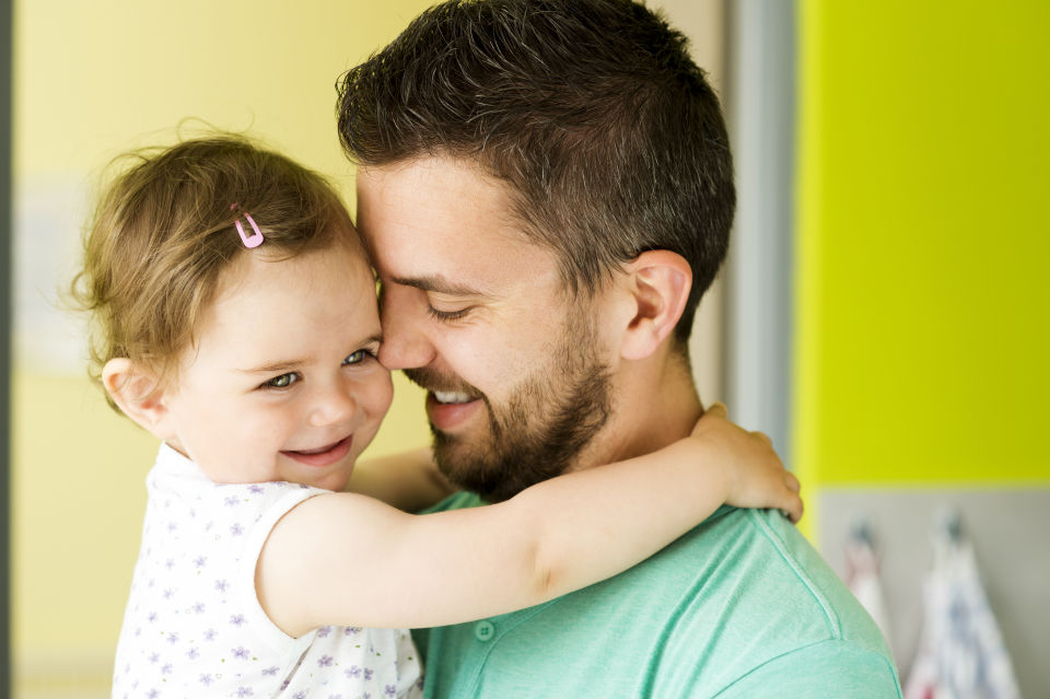 Father with green shirt holding daughter both smiling