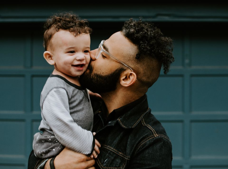 Father holding and kissing baby on cheek