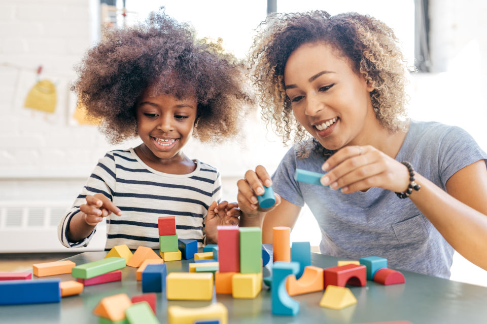 Mom Daughter building with colorful blocks