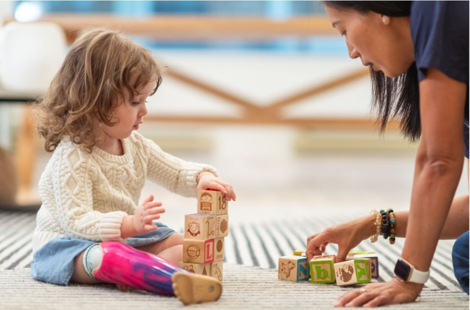 Girl in classroom playing with wood blocks