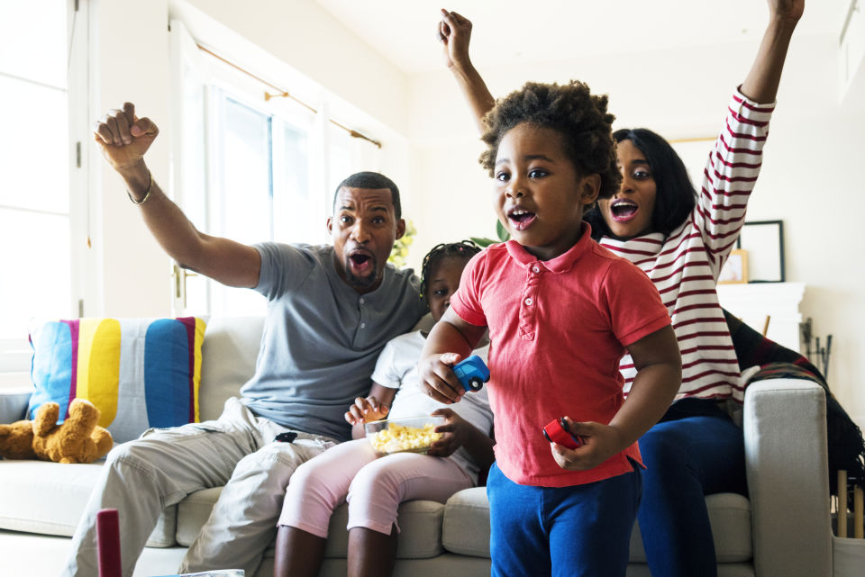 Family Cheering on watching TV in living room