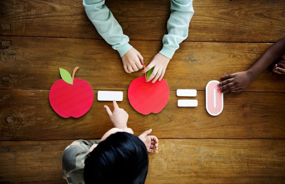 Kids using paper apple cut outs to learn math