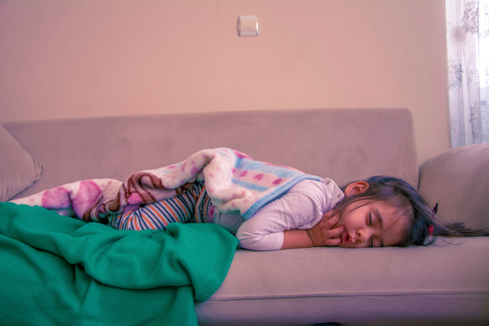 Girl sleeping on couch with green blanket