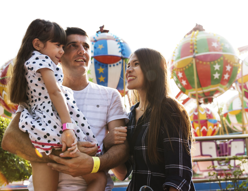 Father holding daughter at amusement park, mother smiling