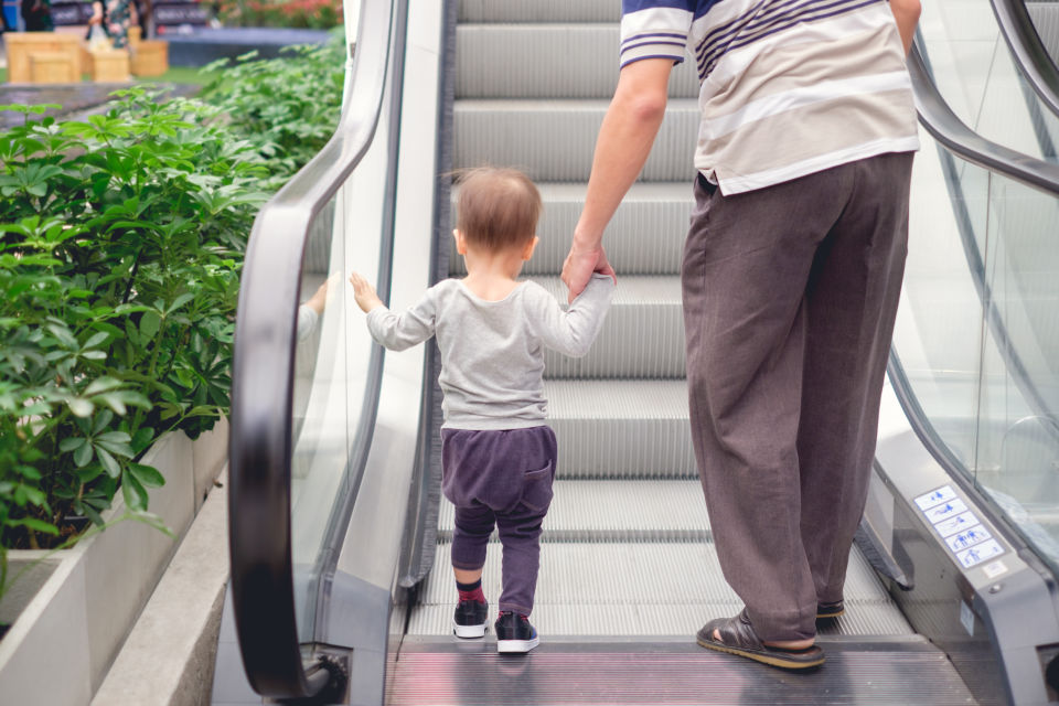 Father Holding boys handing before riding escalator
