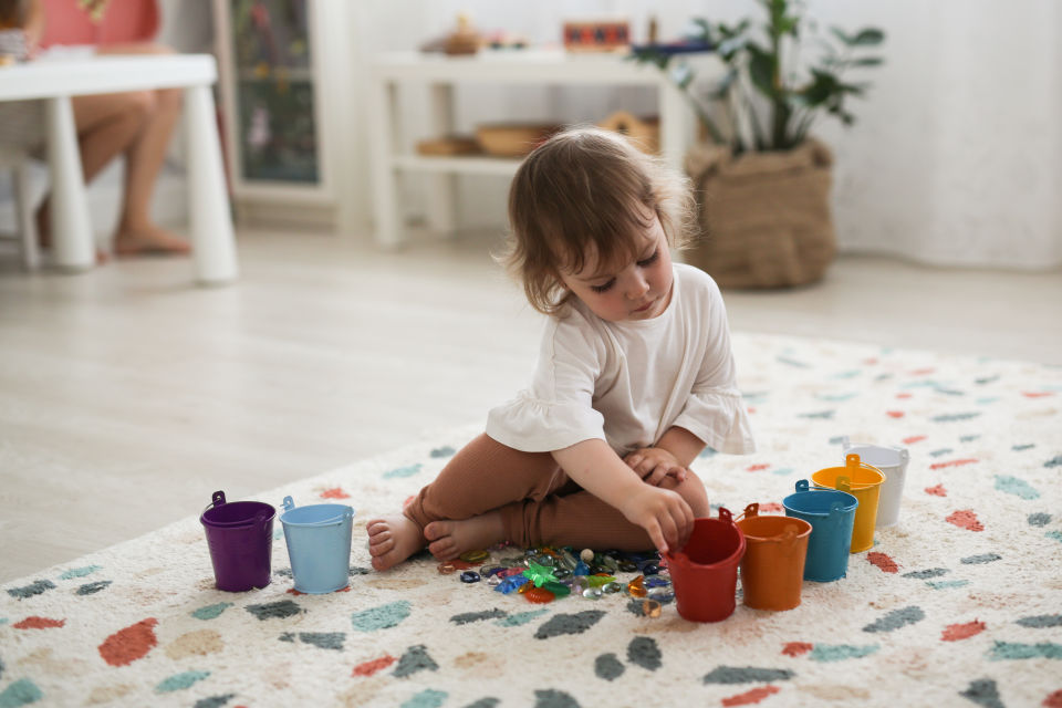 Girl on floor playing with toys