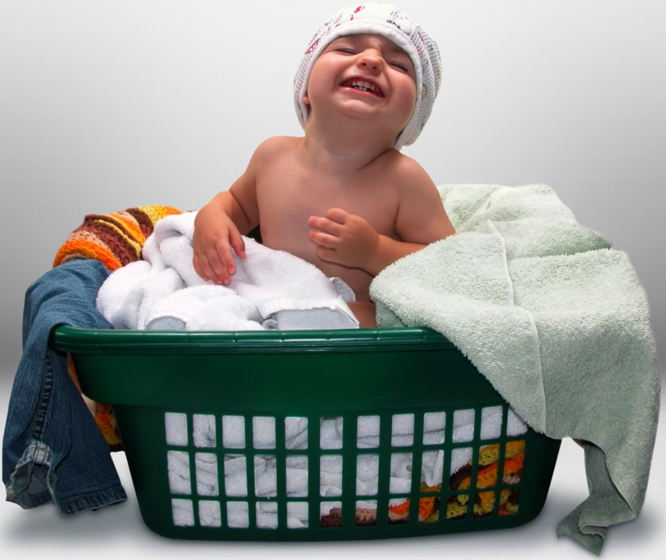 Boy in clothing basket smiling at camera