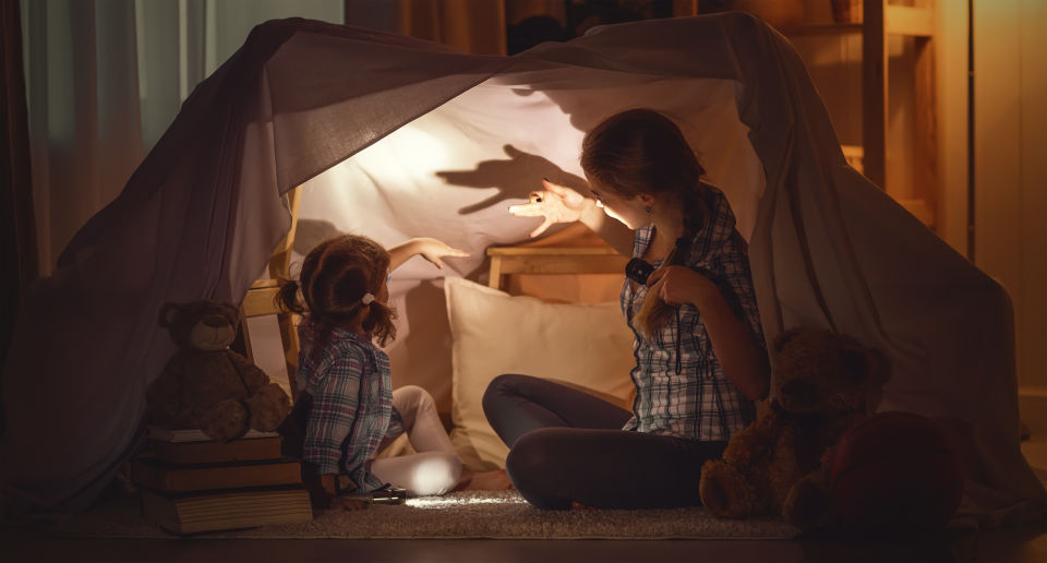 Mom and daughter in fort making hand shadows