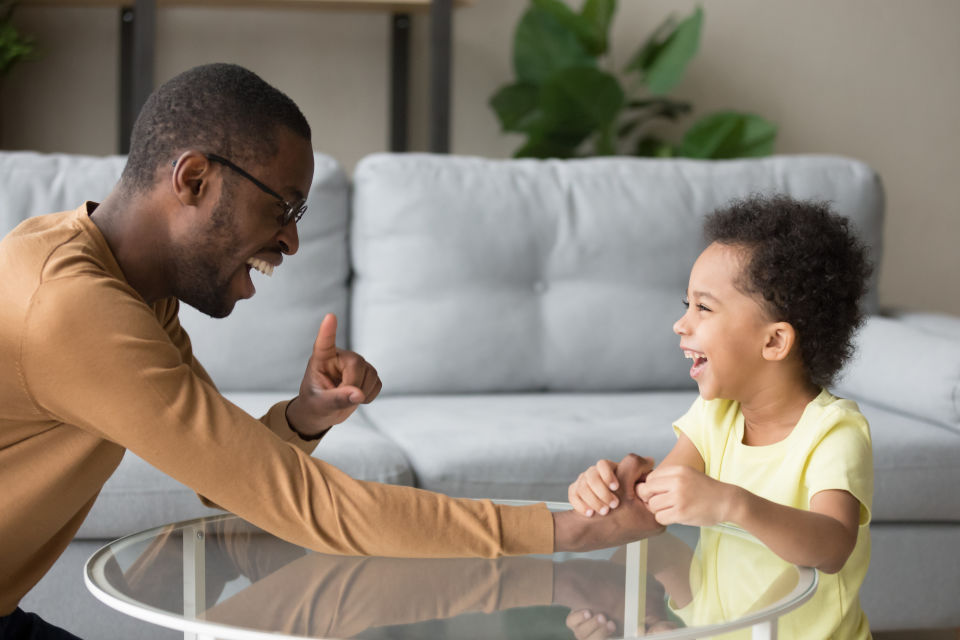 Dad with glasses holding childs hand across glass table